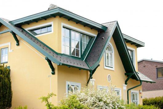 Bestehendes Gebäude mit Eternitdeckung, aufgestockt in Holzriegelbauweise und mit einem EPDM-Flachdach versehen: Altes Dach nur im Vorsprungsbereich erhalten; Sämtliche Anschlüsse von Alt- auf Neubau stilkonform gestaltet
